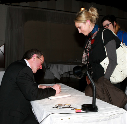 "John Hooton autographing a copy of his first book ""Gathering Light on the Dingle Coast"""
